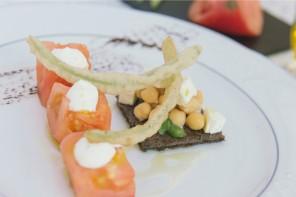 Dados de tomate con salsa de queso sobre bizcocho de olivas negras con guarnicion de ensalada de garbanzos, albahaca y tallos de borraja en tempura